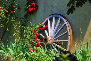 Bild mit romantik, rote Rosen, Nostalgie, Wagenrad, Rad, romantisch, mediteran, mediterran, Landleben, ländlich, nostalgisch, rosenbusch